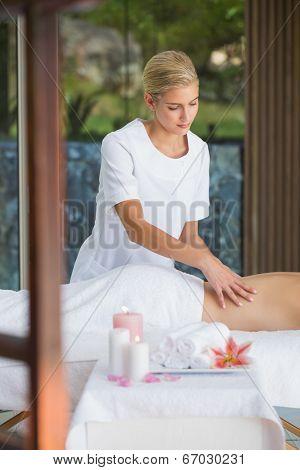 Smiling brunette enjoying a back massage at the spa