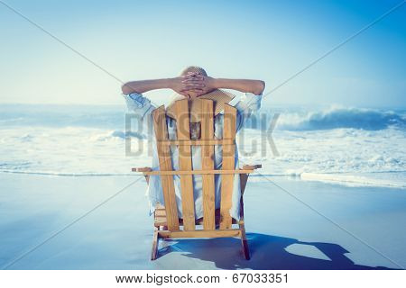 Woman relaxing in deck chair by the sea on a sunny day