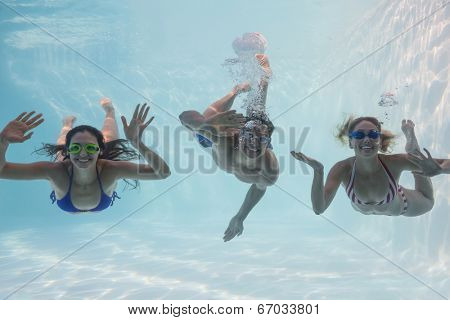 Smiling friends looking at camera underwater in swimming pool on their holidays