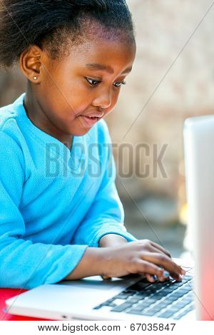 Little African Girl Typing On Laptop.
