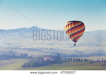 big balloon flies over rural houses Tuscany