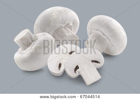 Whole Button Mushrooms And Slices Isolated On Grey Background