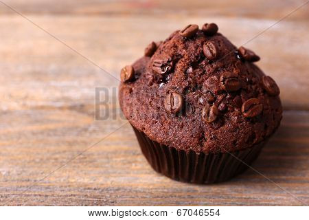 Chocolate muffin and coffee grains on wooden background