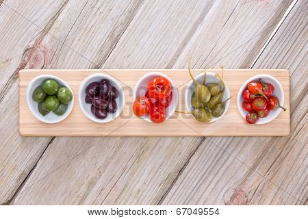 Assorted Olives And Peppers On Taster Plates