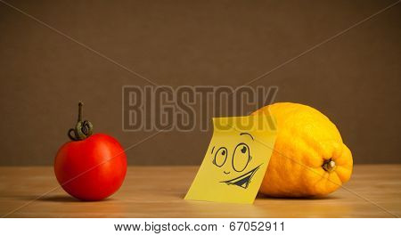 Lemon with sticky post-it note reacting at tomato