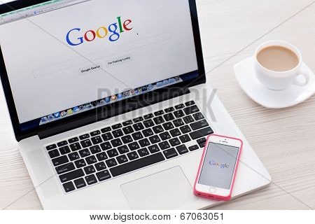 Macbook Pro Retina And Iphone 5S With Google Home Page On The Screen In A White Room