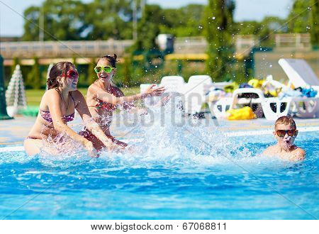 Happy Teenage Kids Splashing The Water In Pool