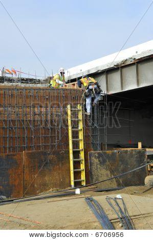 Workman climbs reinforcing bars