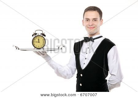 A Buttler Holding A Silver Tray With A Alarm Clock On It