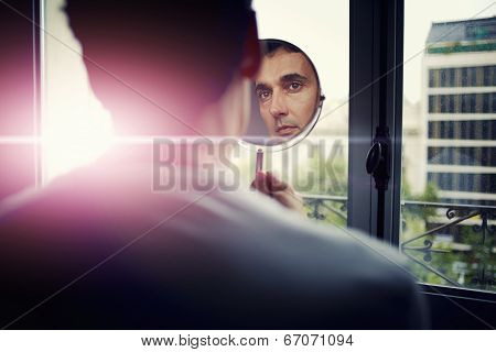 Handsome man looking at himself in a hand mirror
