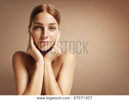 Young Woman Touching Her Face And Looking Stright