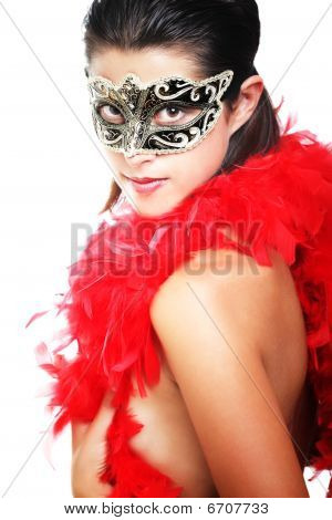 Beautiful young woman in carnival mask and feather boa