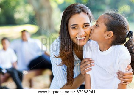 cute little indian girl kissing her mother outdoors