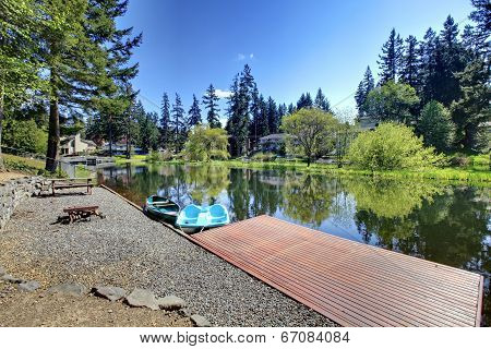 Private Dock With Boats And Patio Area With Rustic Table