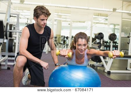 Trainer watching client balance on exercise ball with dumbbells at the gym