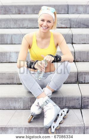 A picture of a rollerblader resting on concrete stairs