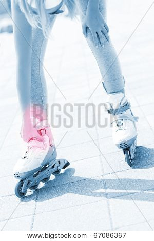 A picture of a woman having problem with ankle while roller blading