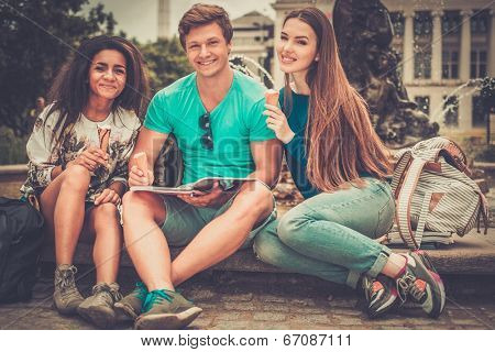 Group of multi ethnic students with ice-cream near fountain in a city park