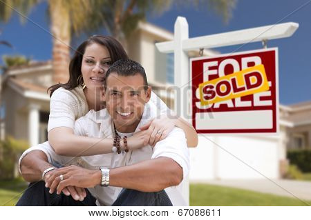 Young Happy Hispanic Young Couple in Front of Their New Home and Sold For Sale Real Estate Sign.