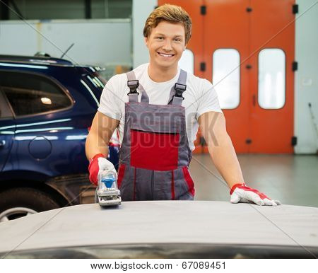 Young serviceman performing grinding with machine on a car bonnet in a workshop