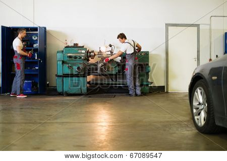 Serviceman working on turning lathe in car workshop