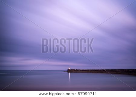 Stunning Long Exposure Landscape Lighthouse At Sunset With Calm Ocean