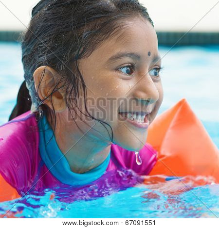 Indian girl learning swimming in pool. Asian child in swimmer class with float bands.