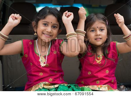 Happy Indian girls sitting in car smiling, ready to vacation.  Asian children.