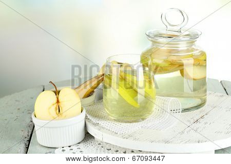 Sangria drink in glass and jar on wooden table, on light background