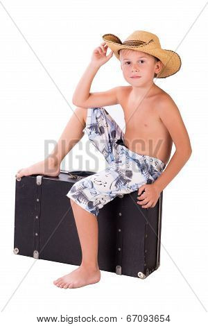 Little Boy Traveler In Hat Sits On Suitcase