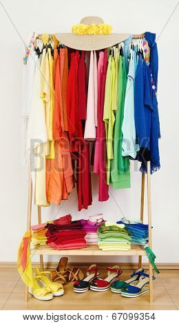 Wardrobe with summer clothes nicely arranged by colors.