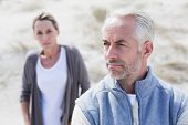 stock photo of not talking  - Couple not talking after argument on the beach on a bright but cool day - JPG
