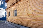 pic of fragmentation  - Fragment of the wall of an apartment house lined with varnished planks block house - JPG