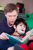 stock photo of storytime  - Father reading book with disabled son with surprised expression - JPG