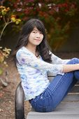 image of biracial  - Young biracial preteen girl ejoying outdoors sitting on wooden park bench - JPG