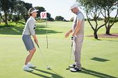 foto of ladies golf  - Lady golfer on the putting green at the eighteenth hole with partner on a sunny day at the golf course - JPG