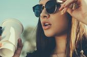 stock photo of hot coffee  - Pretty hipster girl in sunglasses with cup of coffee - JPG