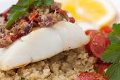 picture of halibut  - Baked halibut with olive tapenade crust garnished with couscous fried cherry tomatoes and fresh parsley.
