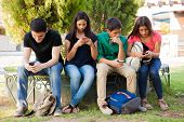 foto of ignorant  - Group of teenage boys and girls ignoring each other while using their cell phones at school - JPG