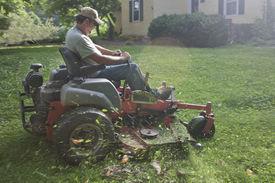 stock photo of grass-cutter  - Landscaper cutting grass on riding lawn mower  - JPG