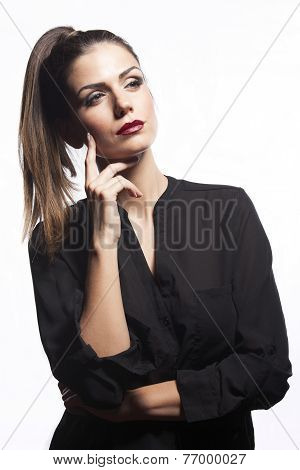 Pretty Young Woman With Ponytail And Red Lipstick And Make Up, With Finger On Her Cheek, In Black Sh