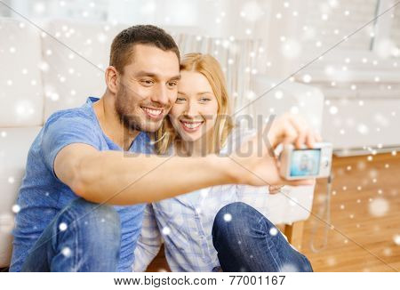 love, family, technology and people concept - smiling couple taking selfie with digital camera at home