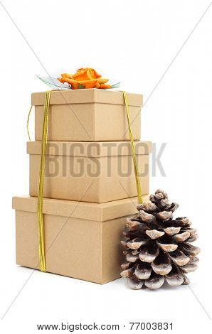 a pine cone and some gift boxes tied with natural raffia of different colors and topped with a flower on a white background