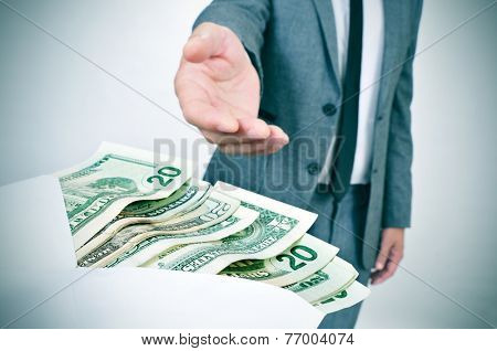 a man in suit taking an envelope full of dollar bills