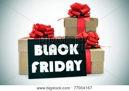 a pile of gift boxes tied with red ribbon and a black signboard with the text black friday written in white