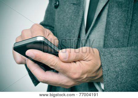 a businessman wearing a suit and a coat using a smartphone