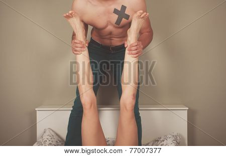 Man Grabbing Legs Of Woman In Bed