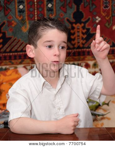 Serious cute little boy raises his finger