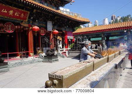 A Worker Cleaning Up Burnt Incense Sticks At The Main Altar Of Sik Sik Yuen Wong Tai Sin Temple