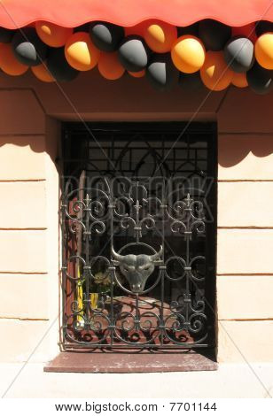 Openwork lattice window with the image of a bull's head